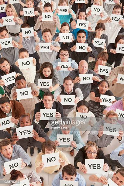 Crowd showing cards saying yes and no