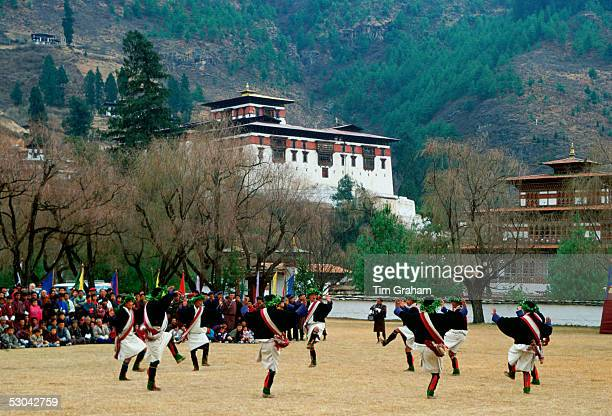 A crowd sit to watch men dressed in traditional costumes dancing as part of a dance festival taking place beside the Paro Dzong a fortress and...
