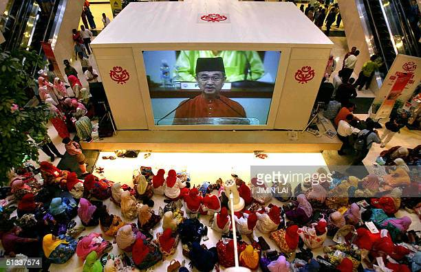A crowd sits on the floor outside a hall as they watch a large screen showing Malaysian Prime Minister Abdullah Ahmad Badawi delivering his opening...