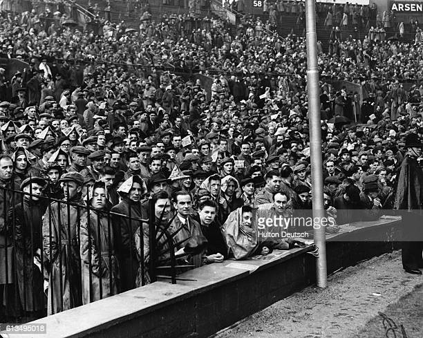A crowd stand in the rain at the FA Cup Final between Liverpool and winners Arsenal at Wembley London in 1950