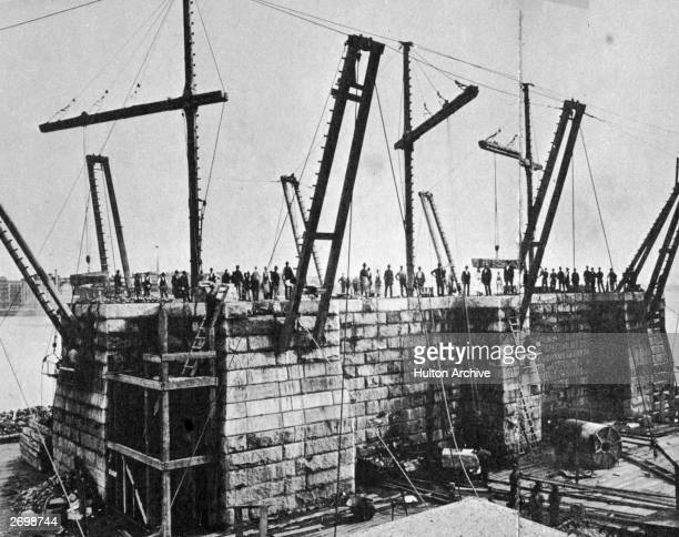 Crowd stands on the early foundations of the Brooklyn Bridge in New York, 21st September 1872.