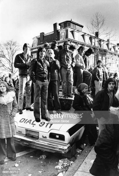 A crowd stands on top of a Boston Police cruiser in front of South Boston High School on Dec 11 1974 A clash between police and a crowd of 1500...