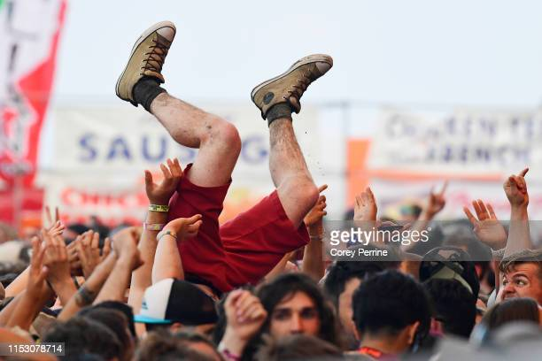 Crowd surfer celebrates Taking Back Sunday's performance as he dips while being passed to the front during the second and final day of Warped Tour on...