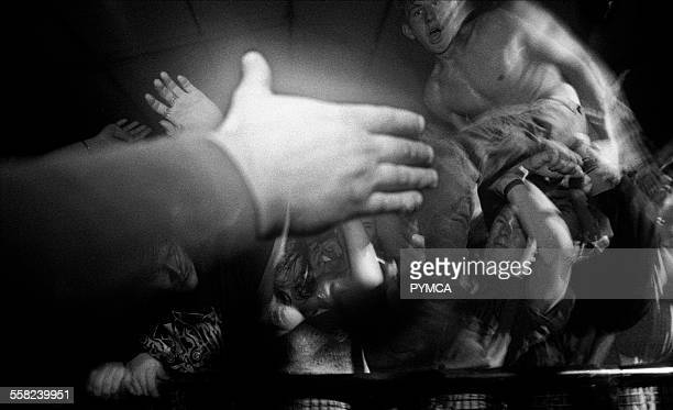 A crowd surfer is offered a hand over the barrier in front of the stage W Australia 1990s