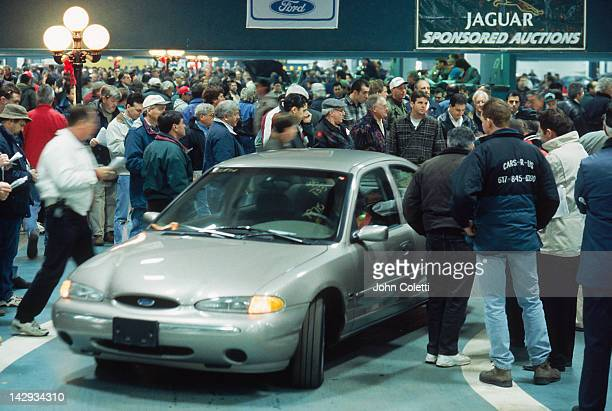 Crowd surrounds a car displayed for an auction