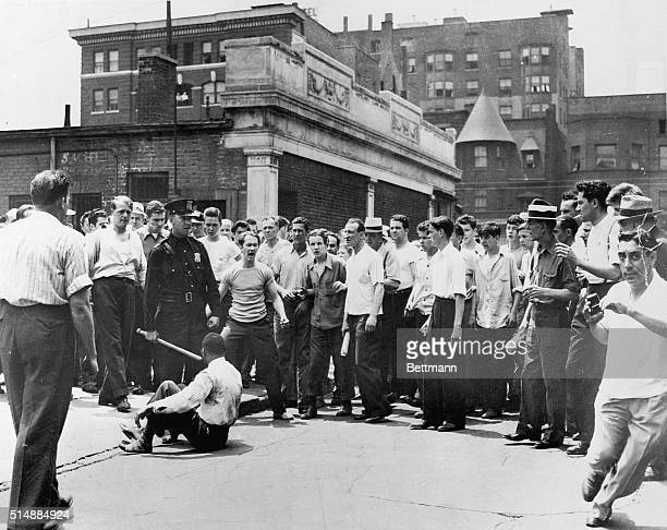 Crowd surrounds an African American assault victim who sits on the street next to a police officer after being hit.