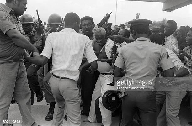 Crowd surrounds members of the fleeing Tonton Macoutes, President Jean-Claude Duvalier's paramilitary police force, at Guy Malary International...