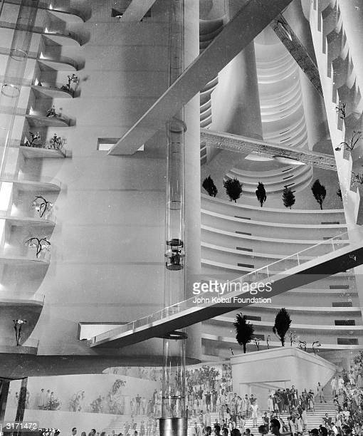 A crowd throngs the ground floor of a futuristic building with trees on platforms set in tiers up the walls From the film 'Things to Come' directed...