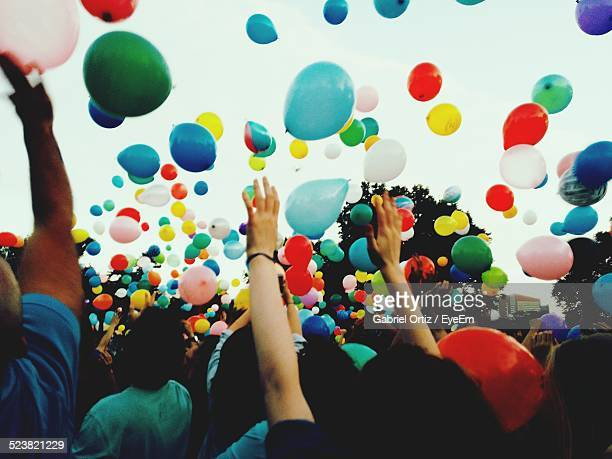 Crowd Throwing Colorful Balloons Against Sky During Festival