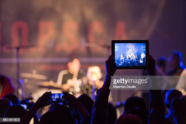 Crowd using tablet PC at rock concert