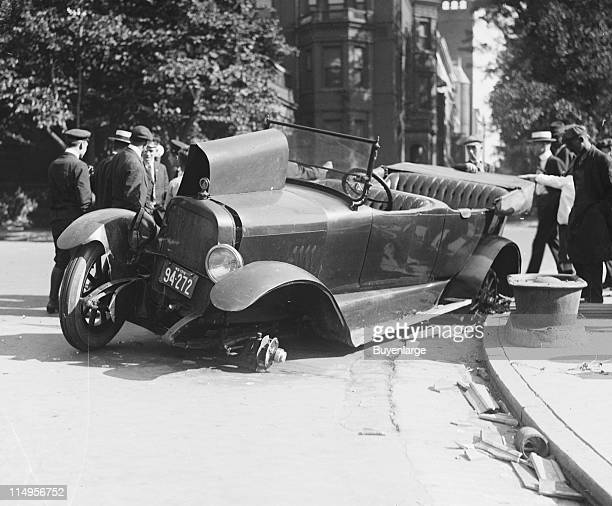A crowd views the scene of an automobile accident early twentieth century The car shows extensive damage and rests on its left side with both wheels...