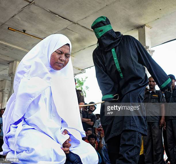 A crowd watch an unidentified punk Indonesian female who was caught having premarital sex in public with a male partner being caned by a sharia...