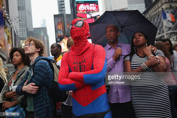 A crowd watches a giant screen in Times Square as US President Barack Obama speaks on the 50th anniversary of Martin Luther King Jr's I Have a Dream...