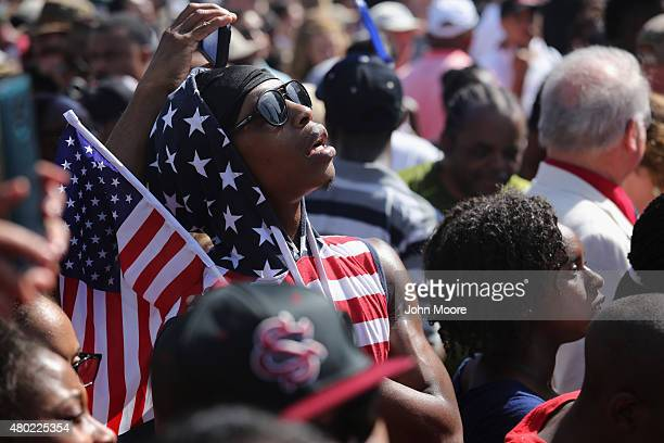 A crowd watches after a South Carolina honor guard lowers the Confederate flag from the Statehouse grounds on July 10 2015 in Columbia South Carolina...