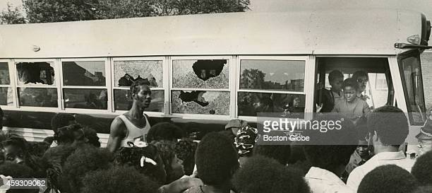 A crowd watches as a bus carrying students returns to Columbia Point with broken windows on Sept 12 the first day of school under the new busing...
