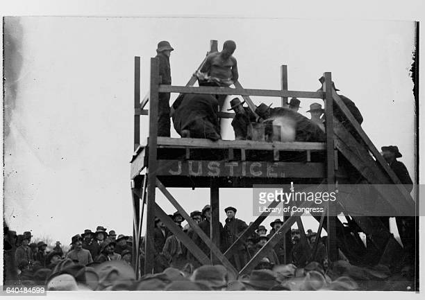 A crowd watches as Caucasian men prepare a platform for the hanging of an African American man named Henry Smith accused of killing a Caucasian girl...