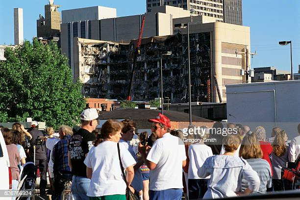 A crowd watches as investigators search the remains of the Alfred P Murrah Building
