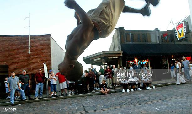 Crowd watches one of a group of children perform flips along Beale Street during Elvis Week August 17, 2002 in Memphis, Tennessee. Up to 75,000 fans...