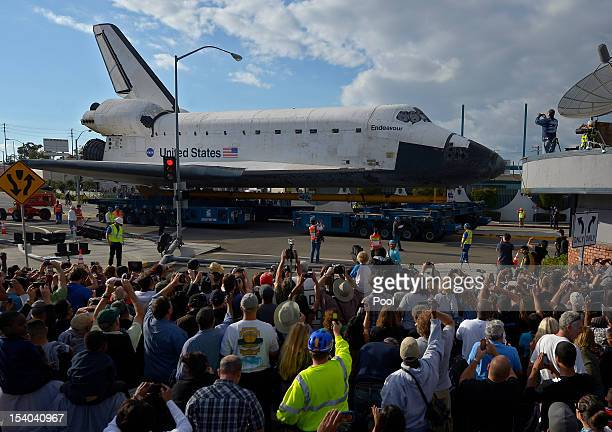 A crowd watches the Space Shuttle Endeavour as it is slowly moved along a city street October 12 2012 in Los Angeles California Endeavour is on its...