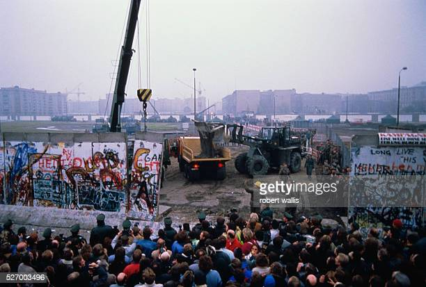 Crowd watches workman deconstruct the Berlin Wall
