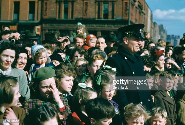 A crowd watching a St Patrick's Day street parade in Dublin Eire June 1955 Original publication Picture Post 7808 Dublin pub 18th June 1955