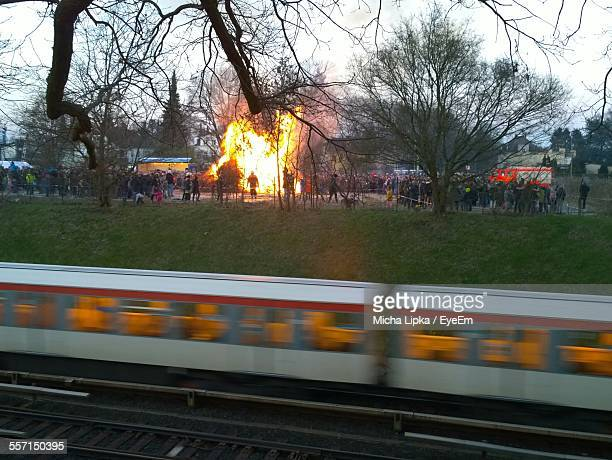 Crowd Watching Building On Fire, Train Passing In Foreground