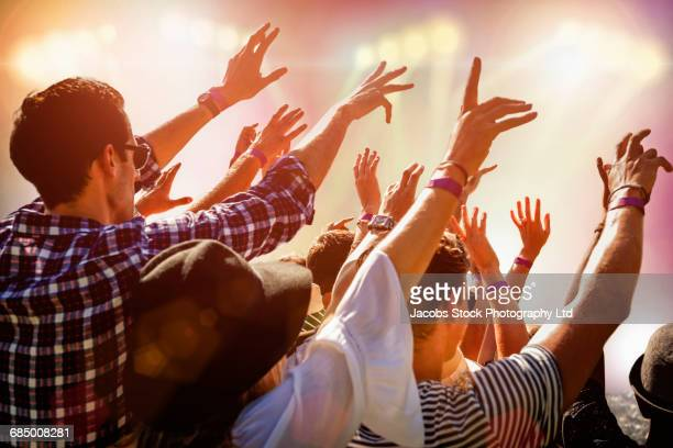 Crowd watching concert with arms raised