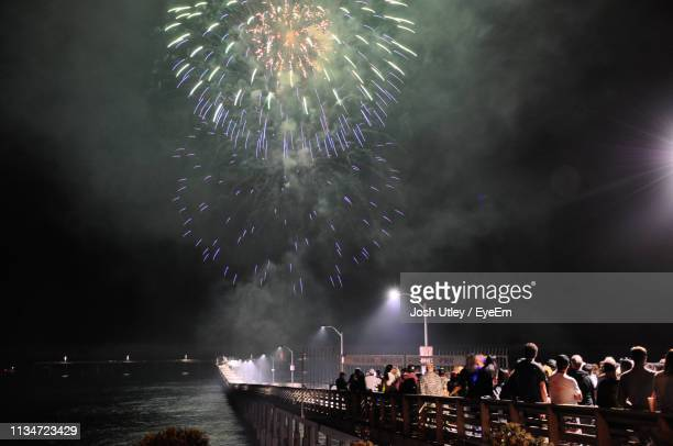 Crowd Watching Firework Display Against Sky At Night