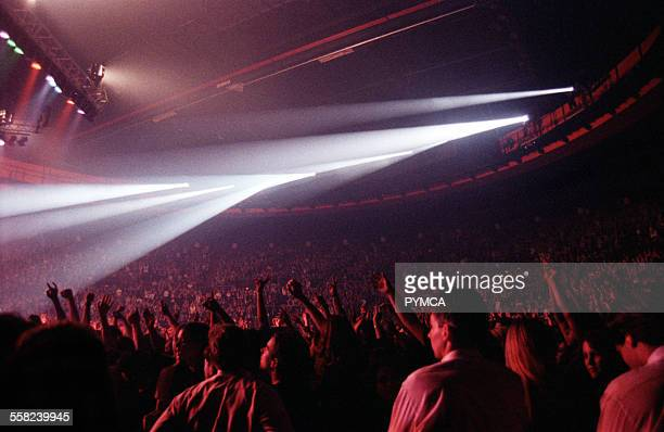Crowd with arms in the air at a large concert arena venue Perth W.Australia 1990s.