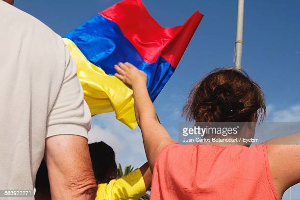 Crowd With Colombian Flag Against Sky