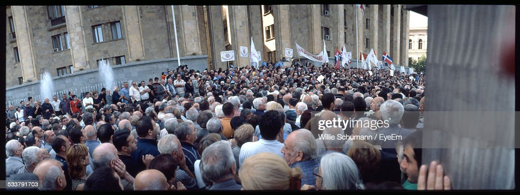 Crowd With Flags And Banners Standing In Front Of Government Building : Foto stock