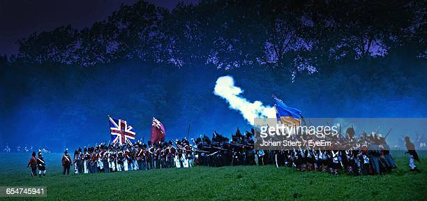 Crowd With Flags For War Standing On Grassy Field Against Mountains