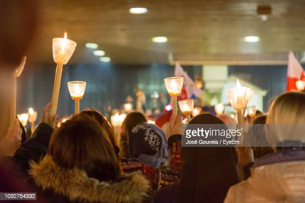 Crowd With Illuminated Candles In Church