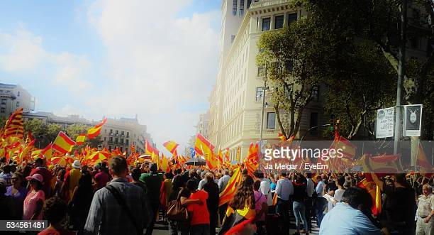 Crowd With Spain Flags On Street In City Against Sky