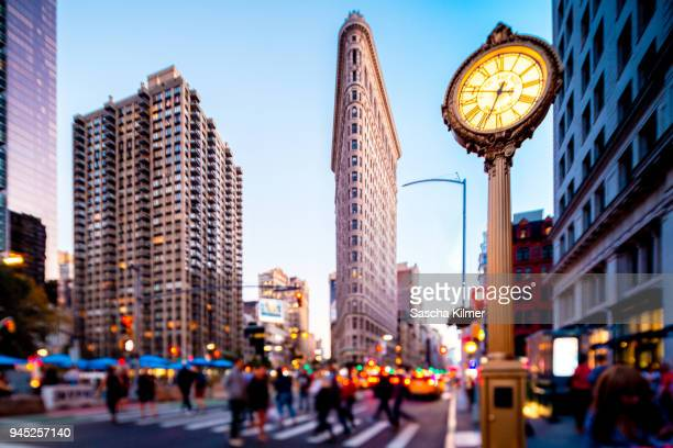 crowded and busy streets below flatiron building, new york - broadway stock pictures, royalty-free photos & images