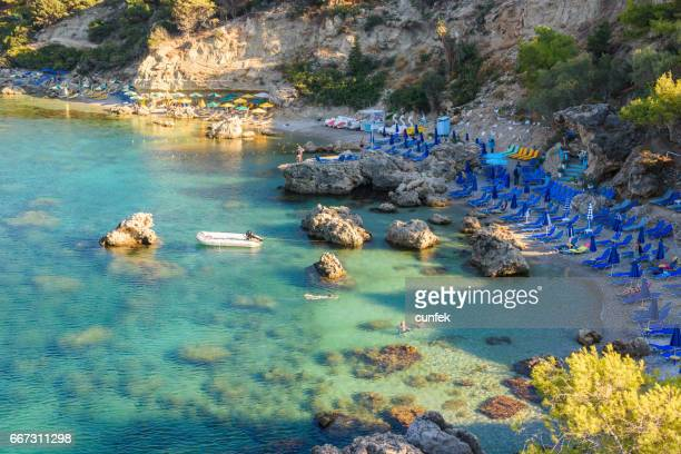 crowded anthony quinn beach, rhodes - dodecanese islands stock photos and pictures