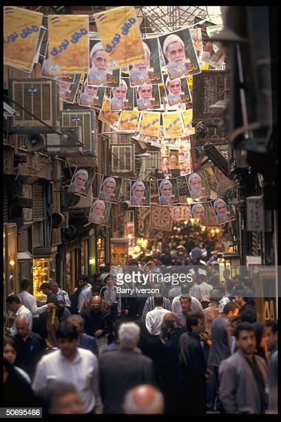 Crowded bazaar w presidential election campaign posters picturing conservative cleric candidate Ali Akbar NateqNoori strung overhead