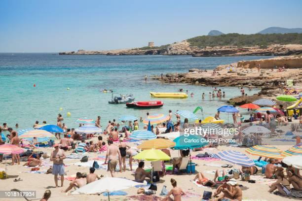 crowded beach during summer in ibiza, spain - tourismus stock-fotos und bilder
