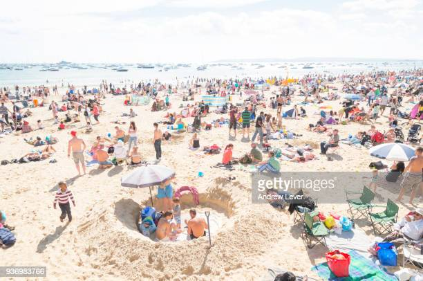 a crowded beach. - crowded beach stock pictures, royalty-free photos & images