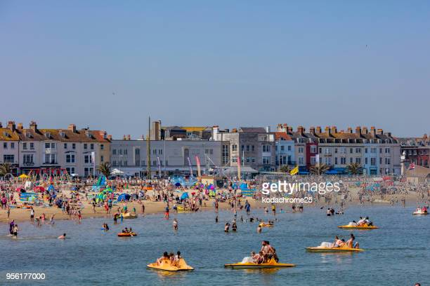 crowded beach sunny hot bank holiday vacation sea - bank holiday stock photos and pictures