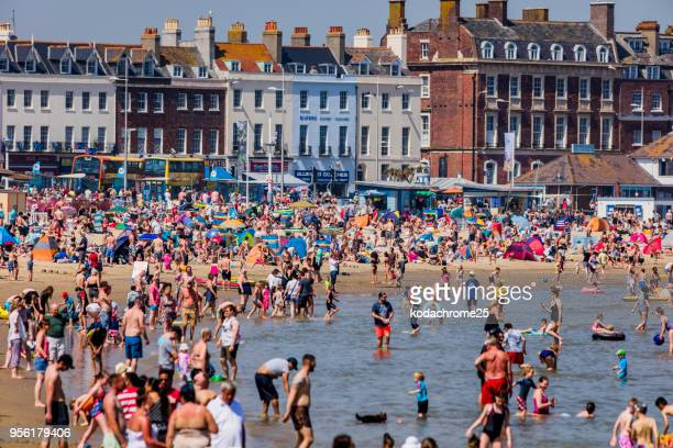 crowded beach sunny hot bank holiday vacation sea - heat wave stock pictures, royalty-free photos & images