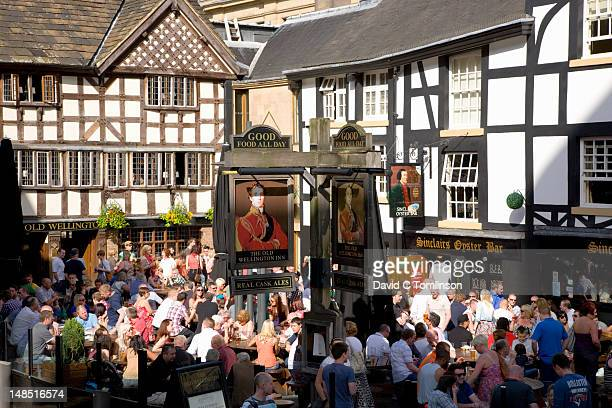 Crowded beer garden of the Old Wellington Inn, half-timbered public house in Shambles Square.