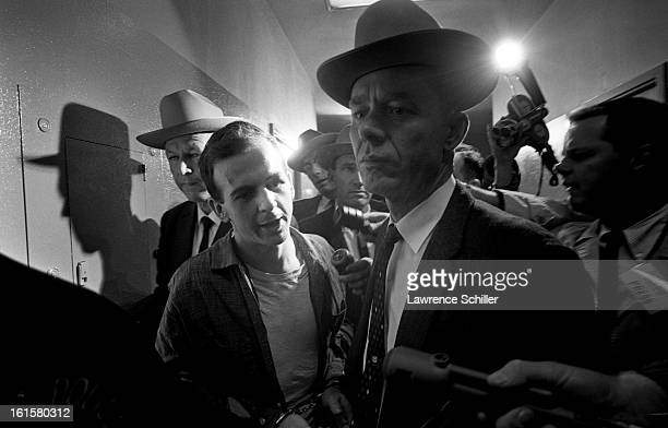 Crowded by police and members of the press, the accused assassin of President John F. Kennedy, Lee Harvey Oswald , is taken down the hall on the...