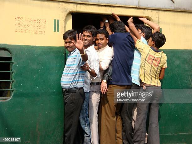 Crowded commuter train, approaching Howrah Railway station, Kolkata, India. Men hang onto the outside of this busy commuter train in Calcutta, India.