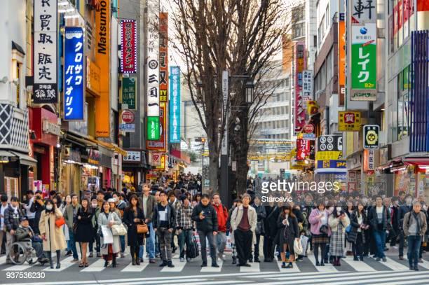 überfüllten tagsüber straßenszene in tokyo, japan - shinjuku bezirk stock-fotos und bilder