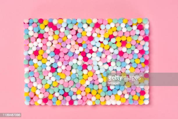 crowded litle fluffy balls on pink - pom pom stock pictures, royalty-free photos & images