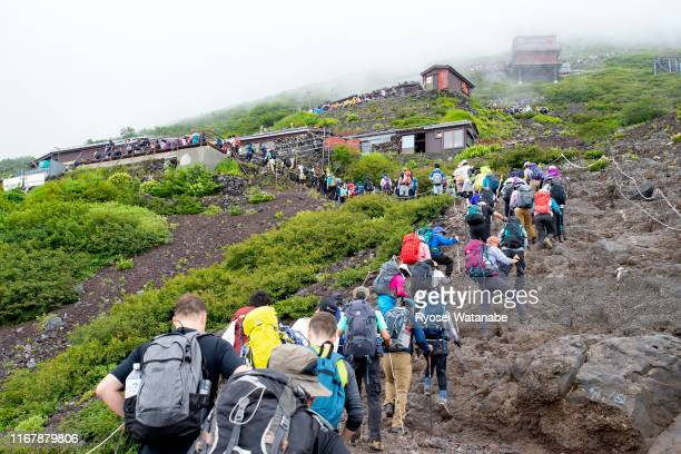 crowded mountain trail in mt. fuji - mt. fuji stock pictures, royalty-free photos & images