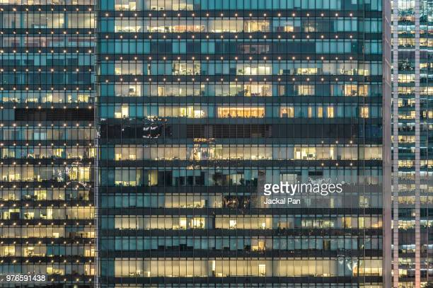 crowded office buildings at night - bürogebäude stock-fotos und bilder