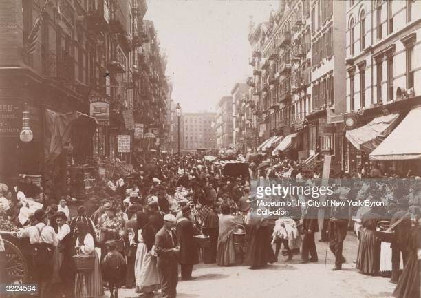 A crowded outdoor market on Orchard Street looking south from Hester Street on the Lower East Side New York City Some of the signs hanging from...
