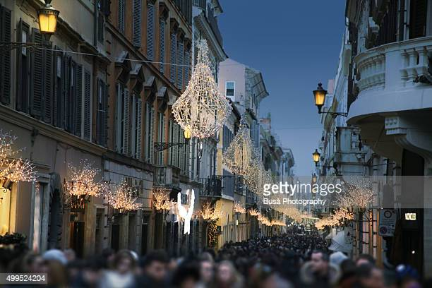 Crowded pedestrian shopping street in the historic center of Rome at twilight